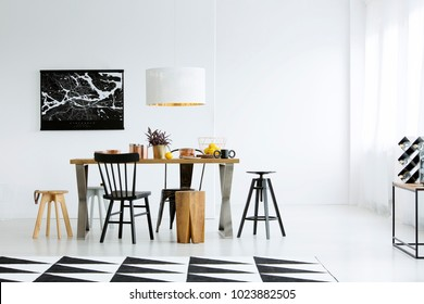 Geometric carpet and black chairs at dining table in bright dining room interior with dark poster on white wall