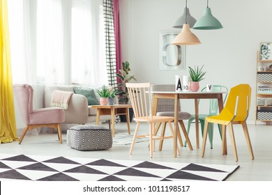 Geometric carpet in colorful living room interior with pink armchair and three lamps hanging above a dining table
