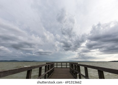 Geometric, first person view of a pier on a lake, beneath an overcast, moody sky