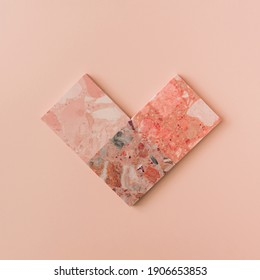 Geometric heart assembly. Pink terrazzo tiles against pale pink background. Minimal flat lay love concept.