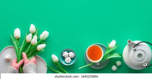 Geometrische Panoramaflaeche liegt mit Händen. Tasse schwarzen Tee, Teekanne, Süßigkeiten und weiße Tulpen auf Grün mit Kopienraum. Valentine, Mutter Tag, internationale Frauen Tag 8. März. Draufsicht, Panoramabild