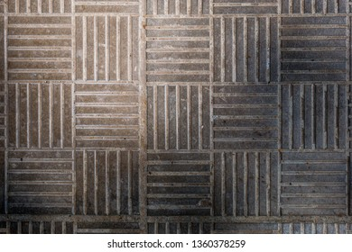 Geometric pattern of concrete pavement tiles with lines partly in shadow. Abstract texture background. Overhead view