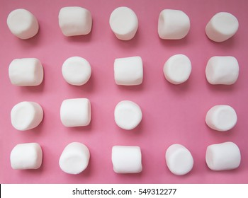 geometric pattern of marshmallows. white marshmallows on a pink background. top view. empty space for your text