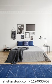 Geometric pattern on a navy blue rug and framed photo gallery on a white wall in an eclectic bedroom interior