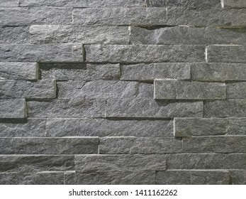 geometric pattern of stone cladding wall, grey color.