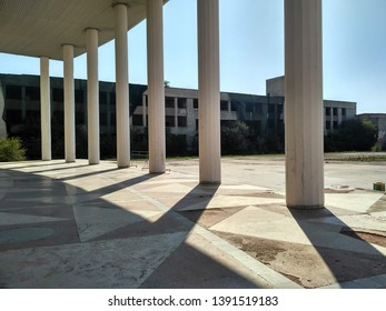 Geometric shadows from the columns in the square against the background of an abandoned building