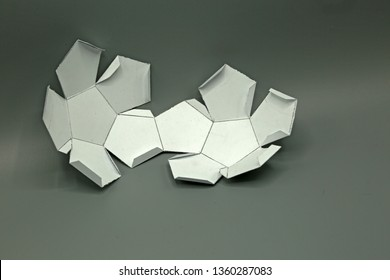 Geometric shape cut out of paper and photographed on grey background.Dodecahedron. 2-dimensional shape that can be folded to form a 3-dimensional shape or a solid.