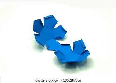 Geometric shape cut out of paper and photographed on white background.Dodecahedron. 2-dimensional shape that can be folded to form a 3-dimensional shape or a solid.