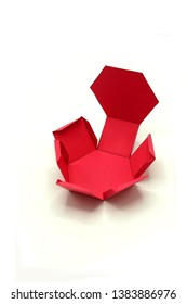 Geometric shape cut out of red paper and photographed on white background.Hexagonal prism. 2D shapefoldable to form a 3-dimensional shape or a solid.