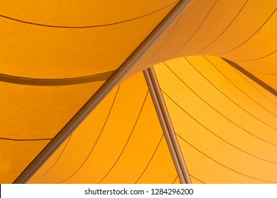 Geometric shaped yellow sails used to provide shade to the forecourt of entranceway