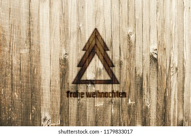 Geometrical Christmas Tree Burned in Wood. Greeting Card with text in German Frohe Weihnachten, in English Merry Christmas.