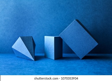 Geometrical figures still life composition. Three-dimensional prism pyramid tetrahedron rectangular cube objects on blue background. Platonic solids figures, simplicity concept photography