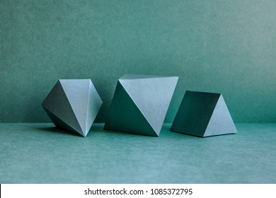 Geometrical figures still life composition. Three-dimensional prism pyramid tetrahedron rectangular cube objects on green background. Platonic solids figures, simplicity concept photography