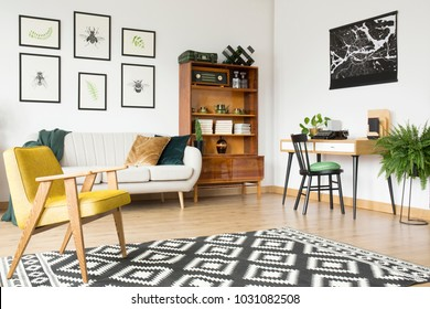 Geometrically patterned rug lying on a wooden floor of a vintage flat interior with beige sofa and cabinet