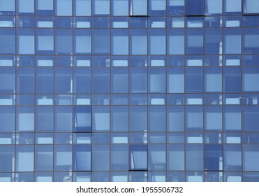 Geometry and abstract reflection of the blue facade. The exterior of modern offices: structure with glass windows.