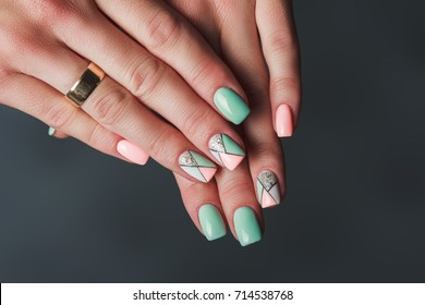 Geometry nail art design in pink and green colors on dark background
