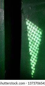 Geometry shadows on green painted wall. Triangle shaped light stain from the window with dotted lattice. Blurred circles of lights inside triangle shadow background. Light and shadow concept