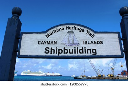 George Town, Cayman Islands: Dec. 5, 2017 – Sign for Maritime Heritage Trail, a driving route through Cayman's maritime sites including lighthouses and shipwrecks. Ships visible in distance.