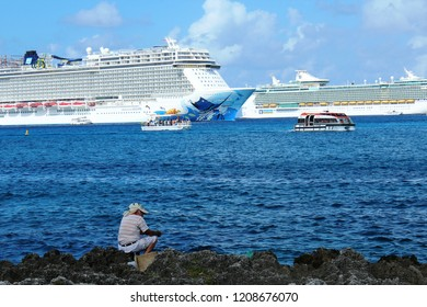 George Town, Cayman Islands: Dec. 5, 2017- Lone fisherman sits and fishes on rocky shores with Norwegian Escape and Royal Caribbean Freedom of the Seas cruise ships and tenders in background.
