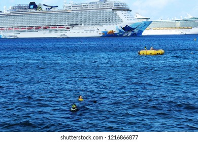 George Town, Cayman Islands: Dec. 5, 2017- Swimmers in water and on large yellow float in foreground with Norwegian Escape, Royal Caribbean Freedom of the Seas cruise ships  in background.