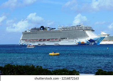 George Town, Cayman Islands: Dec. 5, 2017- Swimmers on large yellow float and tender with tourists in foreground with Norwegian Escape, Royal Caribbean Freedom of the Seas cruise ships  in background
