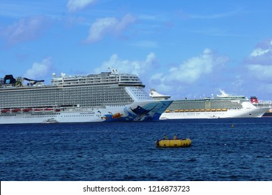 George Town, Cayman Islands: Dec. 5, 2017- Swimmers on large yellow float in foreground with Norwegian Escape, Royal Caribbean Freedom of the Seas cruise ships  in background