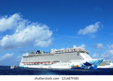 George Town, Cayman Islands: Dec. 5, 2017- Norwegian Escape, Royal Caribbean Freedom of the Seas cruise ships anchored in port at George Town. Tender visible transporting tourists to shore.