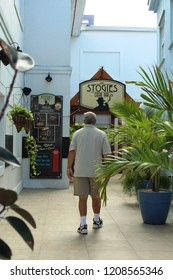 George Town, Grand Cayman: Dec. 5, 2017- Male tourist walks toward colorful shop called Stogies Cigar Bar in the port town of George Town on Grand Cayman in the Cayman Islands.