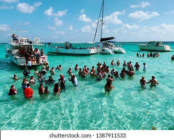 George Town, Grand Cayman, Cayman Island - April 23, 2019: A group of tourists in clear cyan water gather around a stingray while on a excursion from red sail  sports.