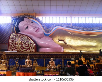 GEORGE TOWN, MALAYSIA - December 10, 2013: tourists are visiting the reclining Buddha statue inside decorated and famous thai buddhist temple in a daylight
