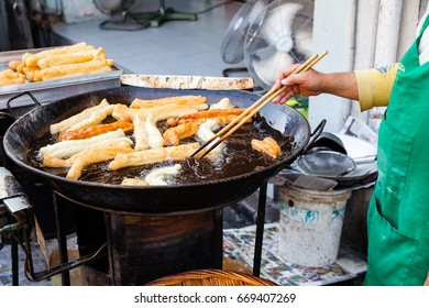 GEORGE TOWN, MALAYSIA - MARCH 23: Man cooks youtiao at the street market of George Town on March 23, 2016 in George Town, Malaysia.