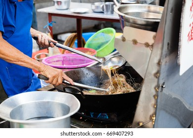 GEORGE TOWN, MALAYSIA - MARCH 23: Chef cooks stir-fried noodles at Kimberly Street Food Night Market on March 23, 2016 in George Town, Malaysia.