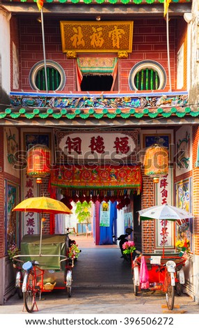 George Town, Malaysia - March 23, 2016: Rickshaw tricycles is parked near the entrance to Hock Teik Cheng Sin Temple on Armenian Street on March 23, 2016 in GeorgeTown, Penang, Malaysia.