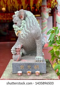 George Town, Malaysia - May 7, 2019: Stone statue of the guardian lion also known as foo dog in front of the Chinese temple.