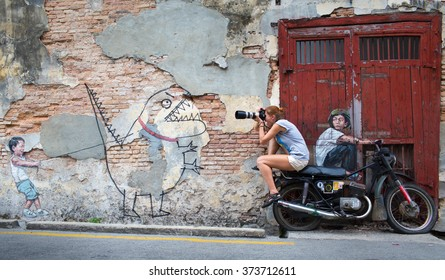George Town, Penang, Malaysia - 04 February 2016: Street art mural with tourist on motorcycle using canon lens to get photo