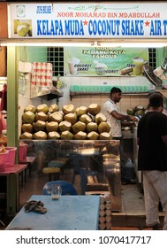 GEORGE TOWN, PENANG, MALAYSIA - FEB 19, 2018: An Indian vendor at his coconut water drink stall in the Padang Kota Lama Food Court in the Esplanade. Coconut water is a popular Malaysian fruit drink.