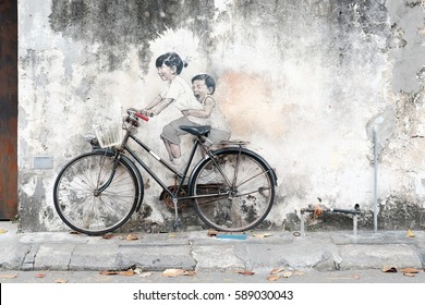 """GEORGE TOWN, PENANG, MALAYSIA - FEB 15, 2017: The Mirror George Town Festival street mural tittle """"Children on bicycle"""" painted by Ernest Zacharevic in Lebuh Armenian."""