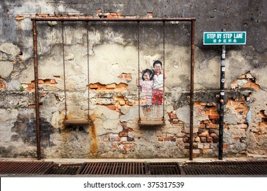 """George Town, Penang, Malaysia - February 11, 2016: Wall artwork called """"Brother and Sister on a swing"""" street art in George Town, Penang"""