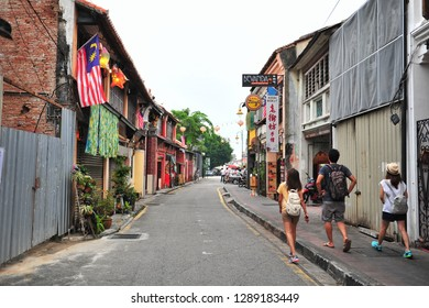 George Town, Penang, Malaysia - January19, 2019: George Town is a popular tourist town, strolling and taking pictures with the Street Art on the old building wall.