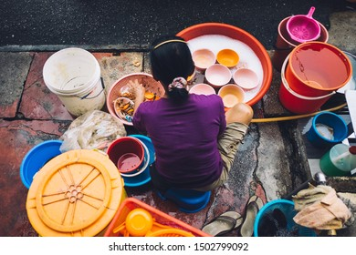 George Town, Penang / Malaysia - July 29 2014: Overhead view of woman washing dirty dishes in buckets on sidewalk for street food restaurant market