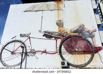 "GEORGE TOWN, PENANG, MALAYSIA - MAY 12 2014 : Street Mural tittle ""The Awaiting Trishaw Peddler"" painted by Ernest Zacharevic in Penang Road, in conjunction with the 2012 George Town Festival."