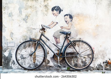 GEORGE TOWN,PENANG ,MALAYSIA- CIRCA March 26, 2015: Public street art Name Children on a bicycle painted 3D on the wall that's two little  girls riding bicycle.  in Georgetown, Penang, Malaysia.