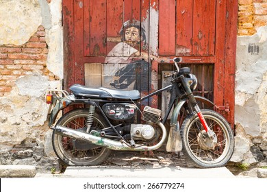 GEORGE TOWN,PENANG ,MALAYSIA- CIRCA March 26, 2015: Public street art Boy on a Bike  on the wall by Lithuanian artist Ernest Zacharevic in Georgetown, Penang, Malaysia.