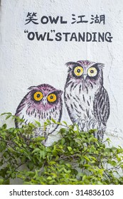 GEORGE TOWN,PENANG ,MALAYSIA- CIRCA September 8, 2015: Public street art Name Owl standing painted 3D on the wall that's two little girls riding bicycle. in Georgetown, Penang, Malaysia