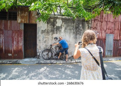 GEORGE TOWN,PENANG ,MALAYSIA- March 26, 2015: Public street art Name Children on a bicycle painted 3D on the wall that's two little Chinese girls riding bicycle in Georgetown, Penang, Malaysia.