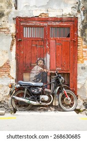 GEORGE TOWN,PENANG ,MALAYSIA- March 26, 2015: Public street art Boy on a Bike  on the wall by Lithuanian artist Ernest Zacharevic in Georgetown, Penang, Malaysia.