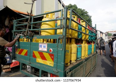 GEORGE TOWN,PENANG, MALAYSIA-21 JUNE 2018: The delivery truck of liquid propane gas in the yellow and green high pressure gasholders. A man deliver it to customers