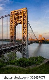 George Washington Bridge crossing the Hudson River connecting Fort Lee, New Jersey and Upper Manhattan, New York City. The towers of the suspension bridge are lit by the sunset light.