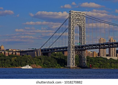 From the George Washington Bridge's New Jersey Side Looking Over Hudson River to New York City During the Golden Hour as the Sun Sets Over A Large Yacht in the Hudson River