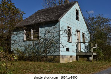 Georgetown, DE/USA-Nov. 9, 2020:  Due to excessive job loss, this sight is common: sky blue cottage, abandoned, neglected, grungy, ruined, ugly, with a broken  screens, windows and leaky roof.